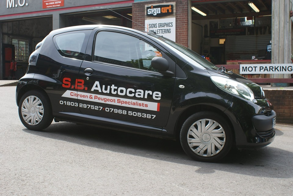 Garage Courtesy Car with white sign writing Newton Abbot & Teignmouth Sign Service